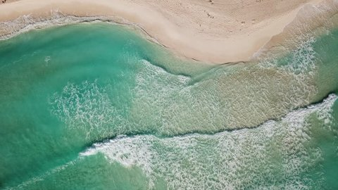 Top view of beautiful beach. Aerial drone shot of turquoise sea water at the beach. Caribbean seaside beach with turquoise water and big waves aerial view.