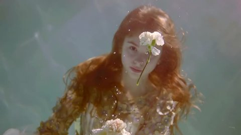 young woman with long red hair underwater like in a fairy tale floats with a bouquet of flowers in her hand