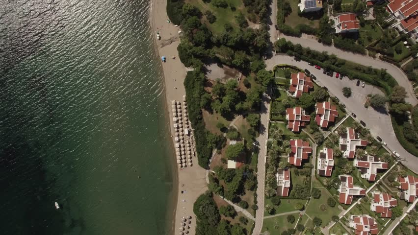 Flying over the sea and coast with cottages and green yards alongside. Sunbeds at the seaside. Living on the shore. Trikorfo Beach, Greece