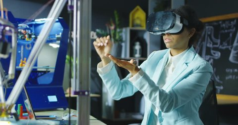 Woman wearing VR headset while working with engineering project in lab with three dimensional printing. Movement 4K shot on Red cinema camera.