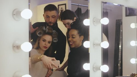 Beauty models together stylist making selfie photo before fashion show in makeup room. Professional makeup and hairdressing for fashion model