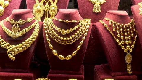 4K view of a set of gold necklaces, chains and bracelets in a showcase of a jewelry store