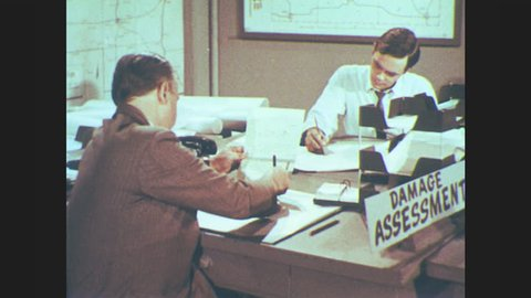 1960s: UNITED STATES: shelter status board. Civil defense drill. Men write bomb hit data on paper. Bulletin board to display data. Lady looks at population graph. Preparation for bomb emergency