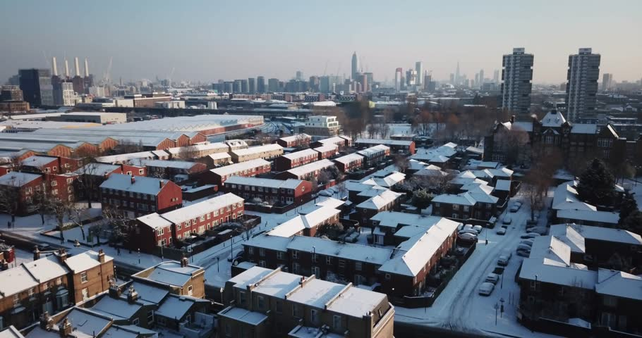Sweeping drone footage of residential buildings in South West London, England, after a rare snowstorm in March.
