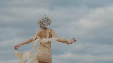 Elegant woman is wearing eccentric suit with waving fabric strips is going out from camera. Back view of her amazing slim body, picturesque clouds in background