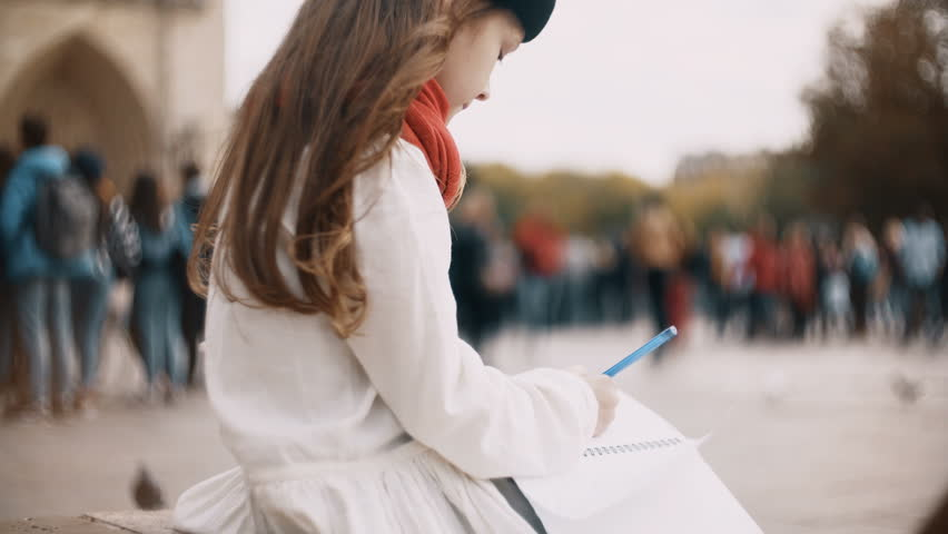 Little beautiful girl with notebook sitting near the Notre Dame in Paris, France and drawing the sketch. | Shutterstock HD Video #1008139387
