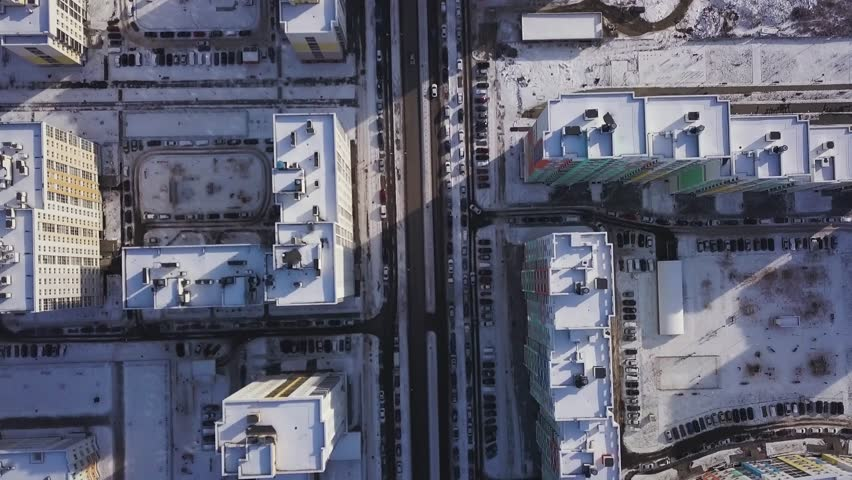 Aerial view snow-covered road with cars in winter. Clip. Aerial view on city in winter day. City panorama with straight road covered with snow from a bird eye view. Winter city streets from a bird eye | Shutterstock HD Video #1008166957