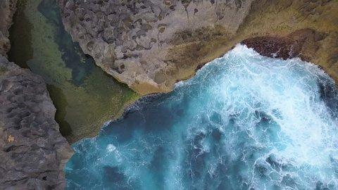 Angels Billabong Natural Pool. Big Blue Sea Waves Crashing on Rock Cliff at Tropical Island. 4K Aerial Travel Footage. Nusa Penida, Bali, Indonesia.