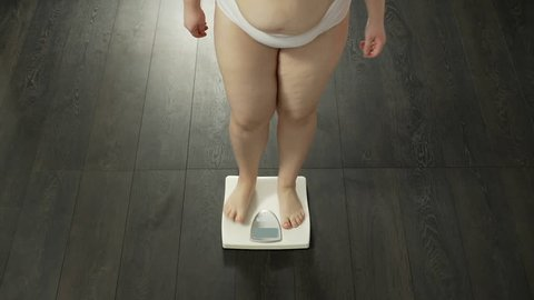 Successful dieting, chubby lady measuring weight, satisfied with results