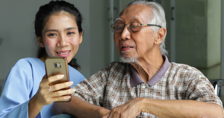 Elderly Asian man sitting on wheelchair and taking selfie photo with his nurse in hospital. Shot in 4k resolution