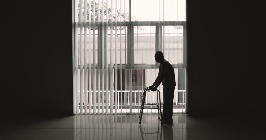 Silhouette of elderly man walking near the window using a walker. Shot in 4k resolution