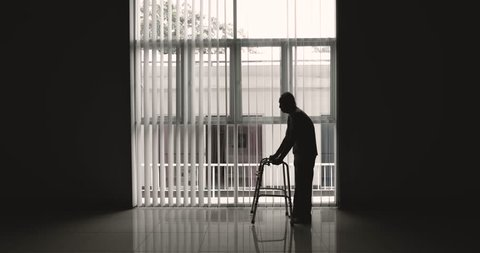 Silhouette of elderly man walking near the window using a walker. Shot in 4k resolution