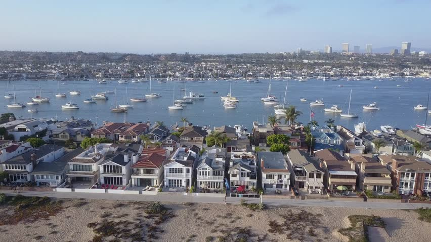 A Panoramic side scrolling aerial view of Newport Beach waterfront homes and harbor.
