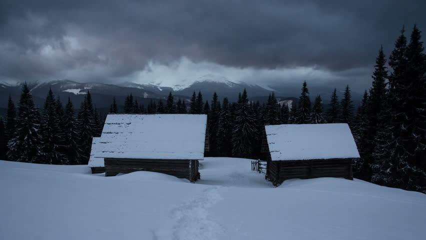 Time lapse thunder clouds moving above winter mountain range dark pine forest log cabin hut house foreground nature landscape
