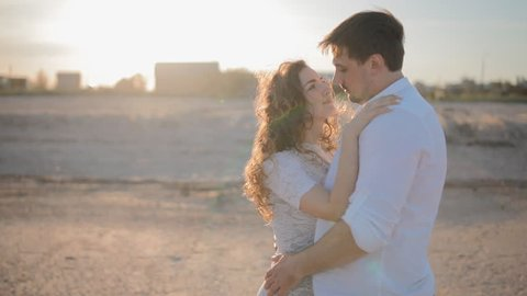 Young white couple in love  on the beach.People look at each other.Man embrace his lady.Woman press to his chest and look at the camera.Slowmotion.Backlight.