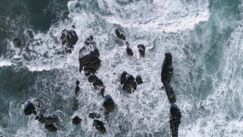 Aerial - Flying above ocean waves crushing into the rocks, top down view