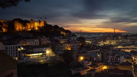 Sunset view of Lisbon old town, Portugal. Roofs of the city, Castelo de Sao Jorge and 25th of April Bridge. Zoom out shot.