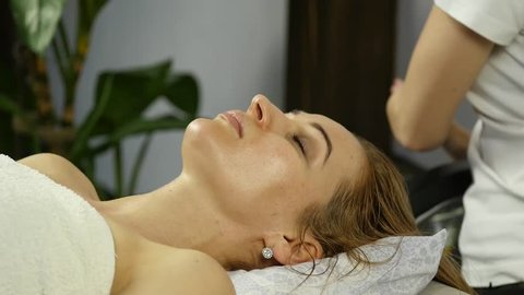 Beautiful woman getting facial massage in spa. facial skin care in beauty saloon. slow motion