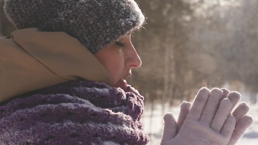 Portrait of a young woman outdoors who is breathing in her arms to keep warm while walking in the winter park | Shutterstock HD Video #1008268657