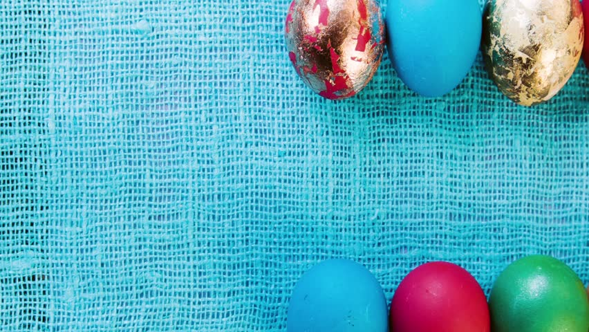 Multicolored beautiful Easter eggs are laid out in two horizontal rows on a cloth lilac, blue tablecloth. Celebratory background for easter. Space for text. Easter eggs closeup.