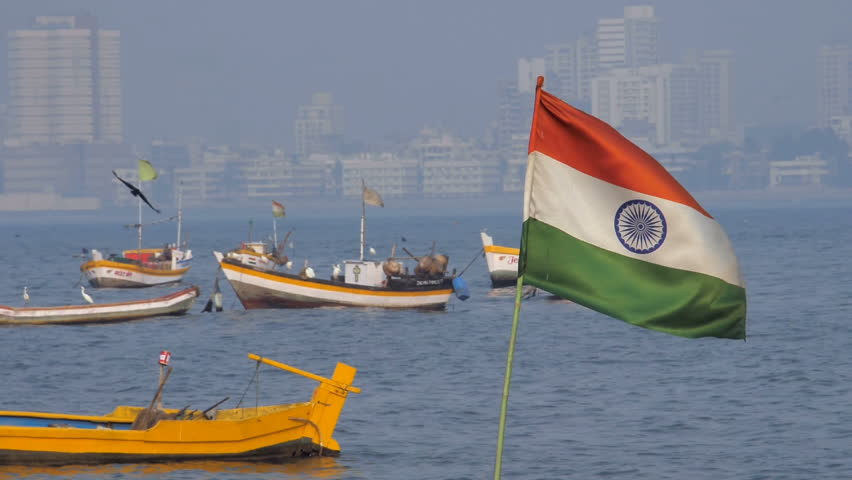 Slow motion shot of a bird flying and Indian flag waving installed on one of the colorful fishing boats parked against city skyline, Mumbai, India