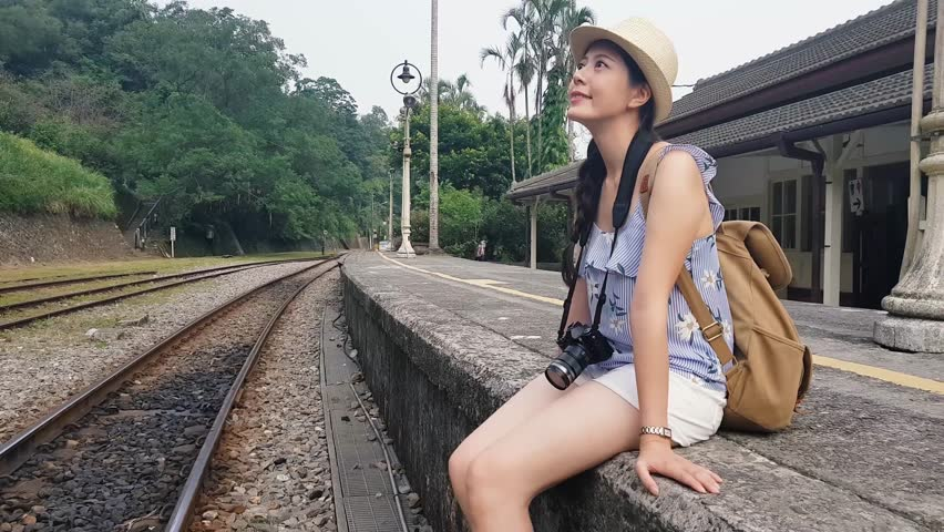 Slow motion of the childlike girl sitting on the stairs beside the old Japanese railway station platform