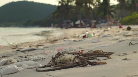 Slowmotion steadycam shot of a beach with fine white sand covered with garbage