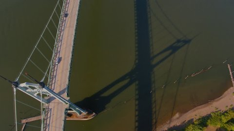 Aerial birds eye view of St Johns Bridge passing over one of the towers in Tower into the river below with the bridge shadow showing in the water