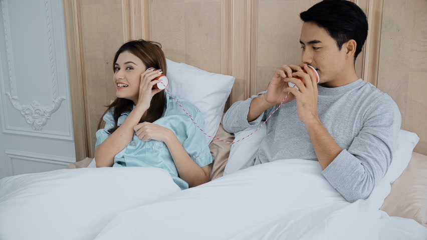 Asian young married couple use can phone to talking together on the bed in bedroom with cheerful