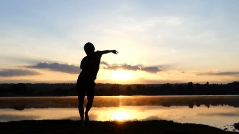 Energetic man dances disco on a lake bank at sunset in slo-mo