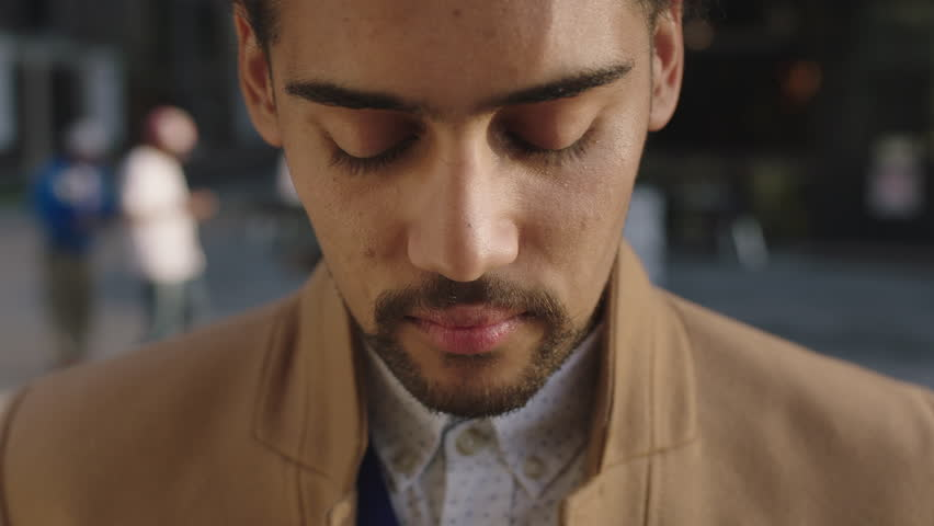 Close up portrait of young mixed race businessman looking up slow motion confident pensive in city real people series
