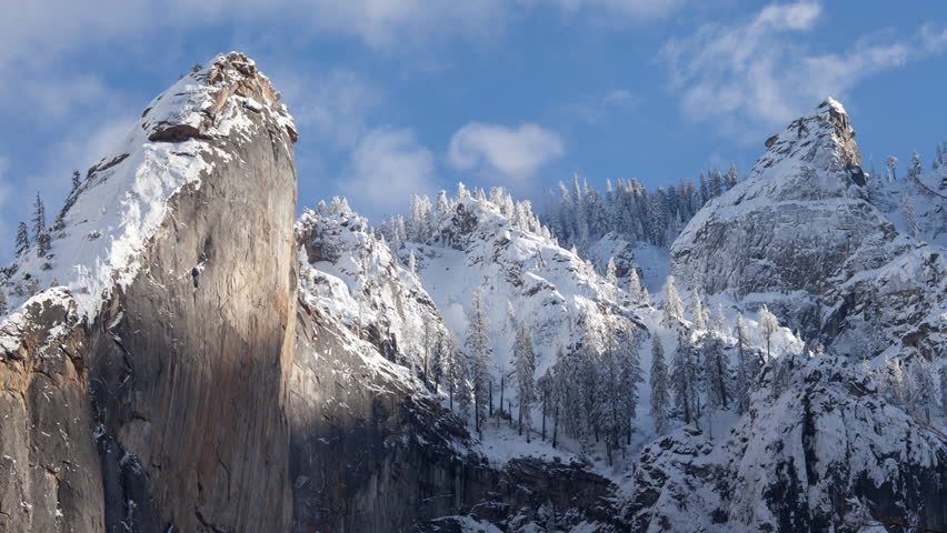 4K time lapse low angle view of blue sky and clouds cresting snow covered mountain tops and trees high in the Sierra Nevada mountains as small avalanches fall in Yosemite National Park in California