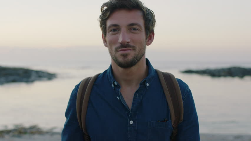 Portrait of attractive charming caucasian man smiling confident on calm seaside beach at sunset wearing blue shirt | Shutterstock HD Video #1008365407