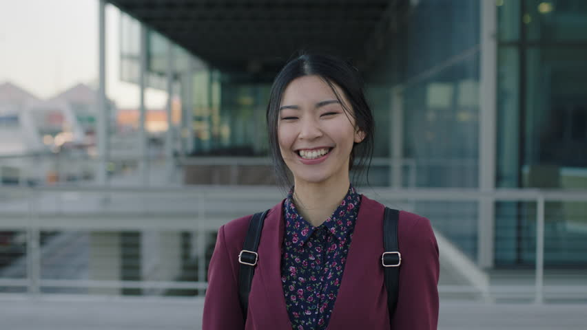 Portrait of young asian woman student laughing happy standing campus university learning