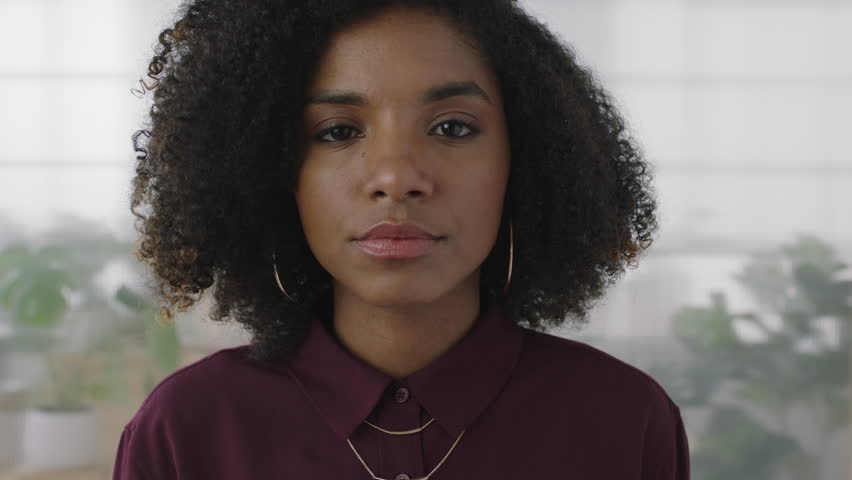 portrait of confident young black business woman intern looking serious at camera independent african american female in office workspace background slow motion