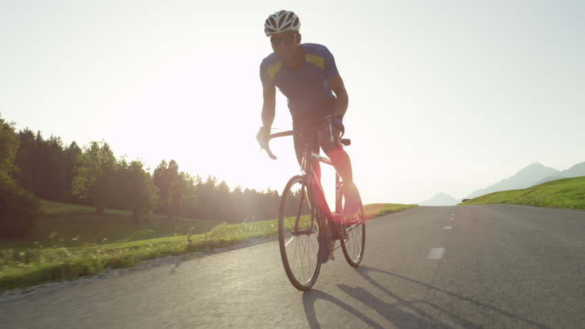 LOW ANGLE LENS FLARE Pro biker man with sunglasses pushes himself to reach the finish line before sunset. Cyclist pedals alone along empty asphalt road. Beautiful summer evening bicycle ride in nature