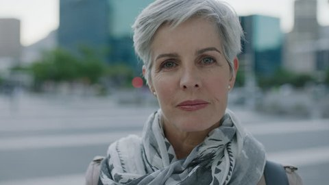 portrait of confident mature caucasian woman looking serious wearing scarf in urban city background modern lifestyle
