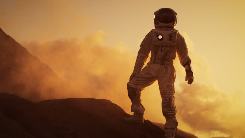Silhouette of the Astronaut Standing on the Rocky Mountain of the Alien Red Planet/ Mars. First Manned Mission on Mars. Space Exploration, Colonization. Shot on RED EPIC-W 8K Helium Cinema Camera.