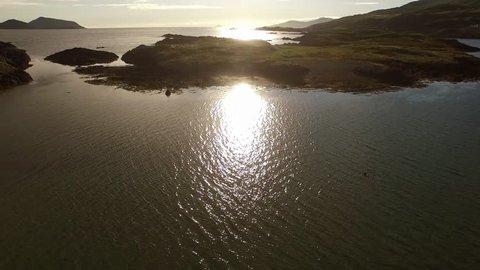 ireland coast, lowpass flight drone towards the sea towards the sun