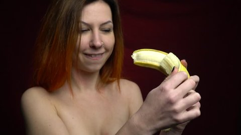 Sexy red-haired girl cleaning a banana standing on a red background, slow motion