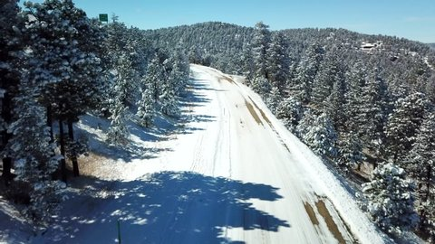 Aerial view of snow covered road through the mountains and trees in Colorado