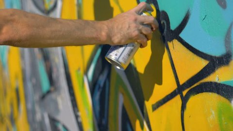 Artist's right hand is painting a yellow letter on the wall, view from the right close up.
