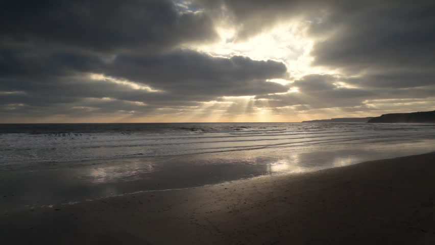 Dramatic clouds at sunrise over Scarborough beach, in Winter.