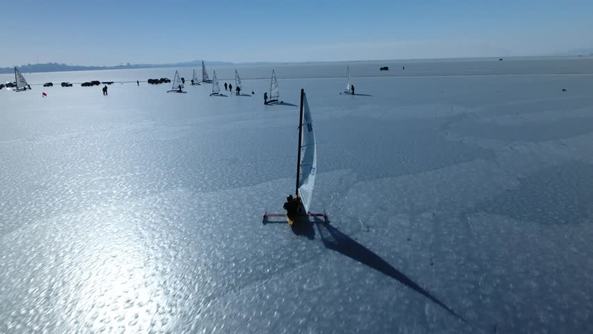 Sailing ships yacht skates on ice skate. Ice-boat sailing. Interesting unusual Unique Sport event competition on cold ice Russia Asia North Baikal. Winter frozen sunny snow day. Blue sky. Aerial above