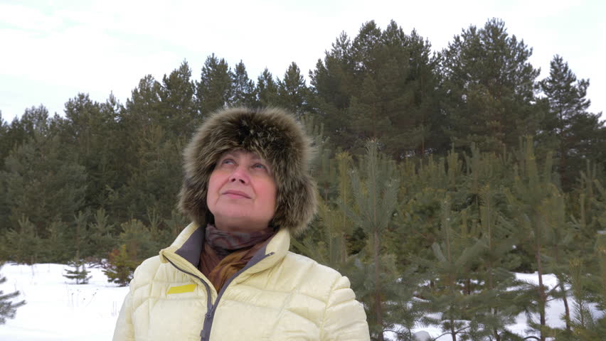 Woman breath with fresh cold winter air in coniferous forest. Adult woman in winter forest.