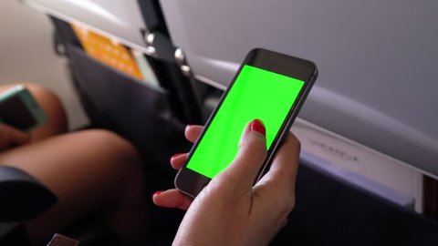Playing mobile phone in aircraft concept,green screen mobile phone touching  by woman hand chroma key screen