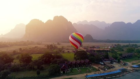 4k Video shot aerial view by drone. River at the village of Vang Vieng on Laos. Sunset landscape Balloon