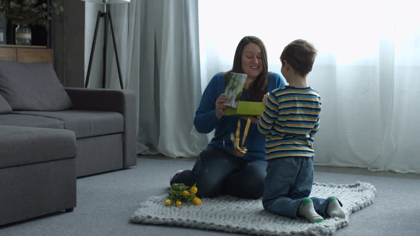 Excited smiling mother receiving a holiday gift box from her loved son on Mother's Day in domestic room. Overjoyed mom opening a present given by her preschool boy on birthday and clapping hands.