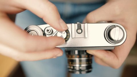 A young photographer changes shutter speed of a vintage old film camera and takes a picture. Closeup shot.