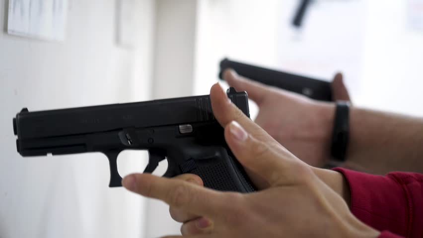 Instructor teaches a man to handle a weapon or gun. Close up of male hands with gun while training with instructor. Close up of man's hand reloading gun
